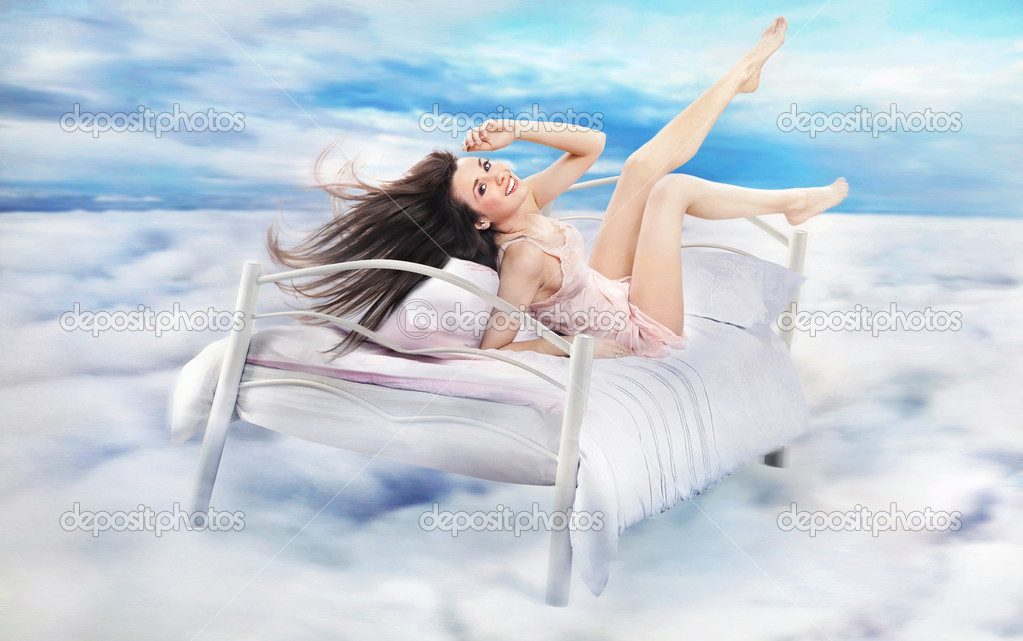 Brunette beauty lying on a bed in clouds  Stock Photo #10681882