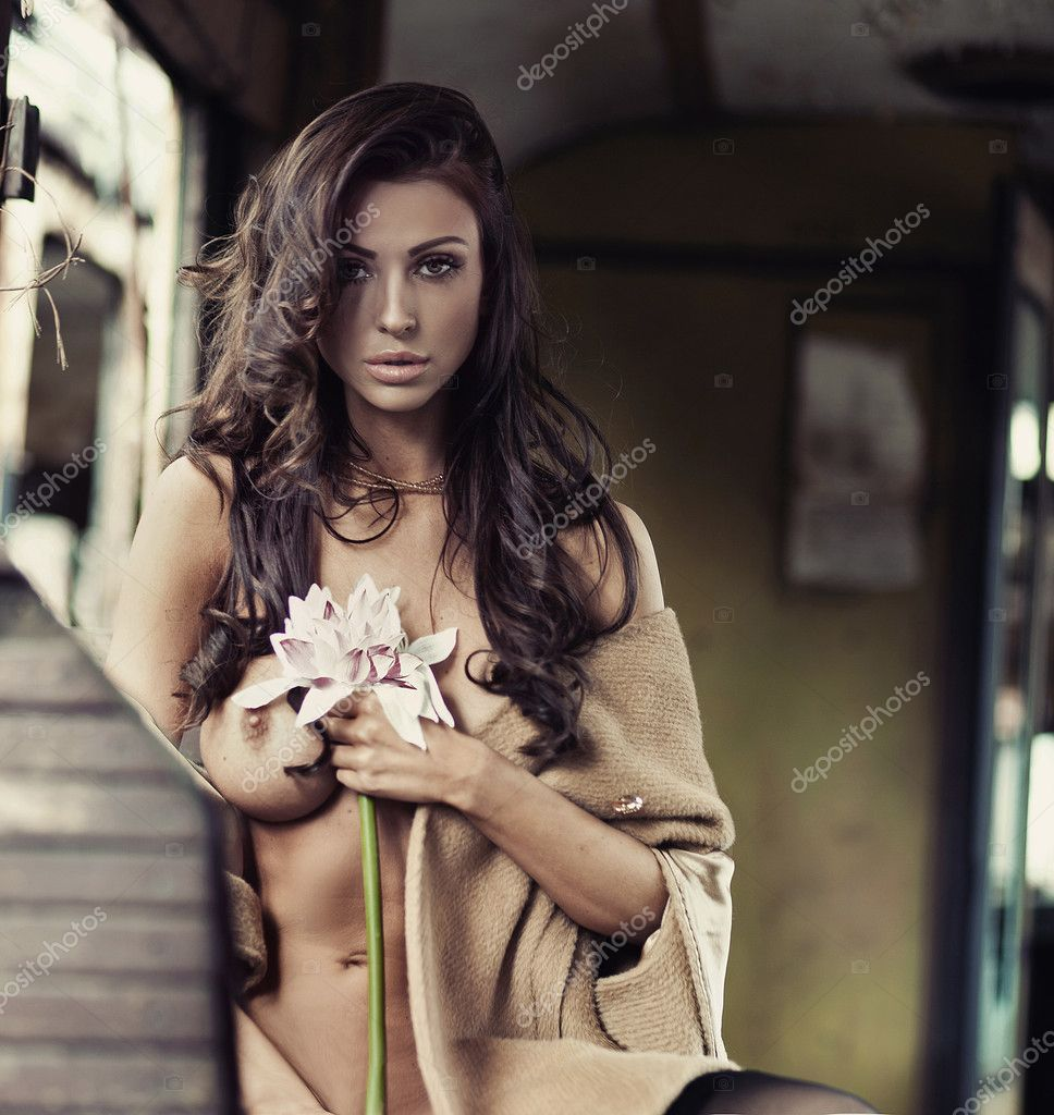 Brunette beauty posing with a flower — Stock Photo #10683919