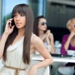 Stunning brunette beauty using cellphone — Stock Photo