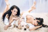 Smiling women lying on the carpet with dog — Stock Photo