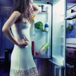 Stock Photo: Womwearing pajamas looking at fridge