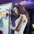Young woman looking at fridge — Stock Photo