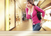 Cute lady looking at a shop window in shopping center — Stock Photo