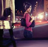 Walking woman looking at shop window — Stock Photo