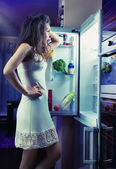 Woman wearing pajamas looking at fridge — Stock Photo
