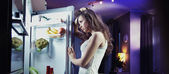 Young woman looking at fridge — Stock Photo