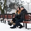 Young couple sitting on bench in park — Stockfoto