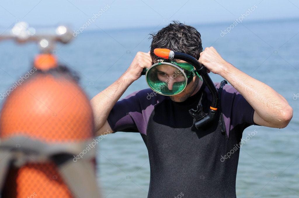 Young man ready for snorkeling. Scuba diving tanks out of focus. — Stock Photo #9138595