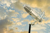 Classic microphone and cloudy sky — Stock Photo