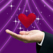 Matchmaker's hand with heart in handheld - Foto Stock