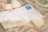 Heart with postcard in the sand — Stock Photo
