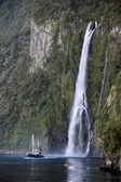 Water fall and boat in the Milford Sound — Stock Photo