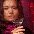 Sad Asian woman with drink in cold rainy weather — Stock Photo #9625420