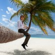 Businessman with tablet pc sitting on palm tree — Stock Photo