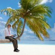 Manager with tablet pc sitting on palm tree — Stock Photo #9625826