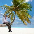Stock Photo: Manager with tablet pc sitting on palm tree