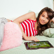 Royalty-Free Stock Photo: Teenage girl laying in bed with tablet computer
