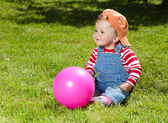 Toddler sit with ball in the garden — Stock Photo