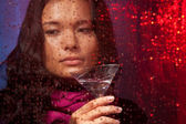 Sad Asian woman with drink in cold rainy weather — Stock Photo