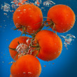 Stock Photo: Bunch of tomatoes underwater
