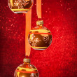 Three Christmas balls on red — Stockfoto