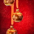 Three Christmas balls on red — Stock Photo