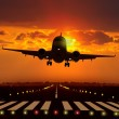 Airplane take off during sunset - Stock Photo