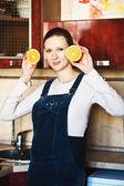 Pregnant woman at kitchen with orange — Stock Photo