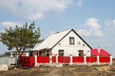 Small house behind red fence — Stock Photo