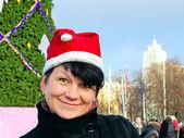 Happy woman in cap Santa Claus near New Year's fur-tree — Stock Photo