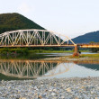 Bridge through mountain river - Stock Photo