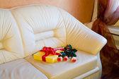 Geschenk und rosenstrauss auf ledersofa — Stockfoto