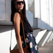 Woman wearing sunglasses with leather bag — Stock Photo