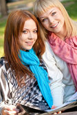 Two sisters looking at camera in the park — Stock Photo
