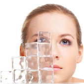 Krásná žena tvář poblíž kostky ledu — Stock fotografie