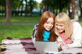 Two sisters with laptop in the park — Stock Photo