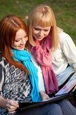 Duas irmãs com álbum de fotos no parque — Fotografia Stock