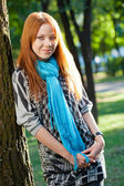 Smilin red-haired woman near tree — Stock Photo