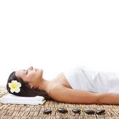 Woman laying on bamboo mat — Stock Photo