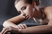 Brunette woman with jewellery looking at camera — Stock Photo