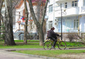 A young man in a hat rides a bicycle — Stock Photo