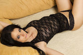 Black haired sexy woman laying between pillows — Stock Photo