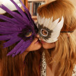 Two beautiful lesbian women kissing in carnival masks — Stock Photo