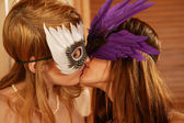 Two beautiful lesbian women kissing in carnival masks — Stock Photo
