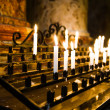 Foto Stock: Burning candles in a church
