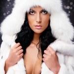 Beautiful woman in white fur coat and cap — Stock Photo