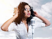 Beautiful young woman with headphones and microphone over clouds — Stock Photo