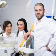 Friendly male dentist, assistant and smiling patient at dental clinic — Stock Photo