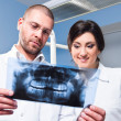Stock Photo: Dentist and assistant checking x-ray at dental clinic