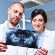 Dentist and assistant checking x-ray at dental clinic — Stock Photo